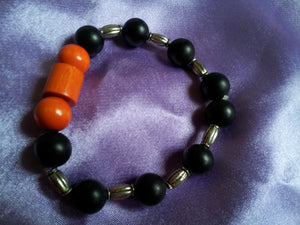 O-Swirl bracelet wood and black onyx surrounds with charm.