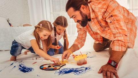 Dad teaching daughters how to use acrylic paint on fabric