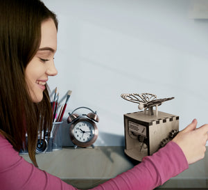 Model shown smiling while cranking wheel of automaton. The automaton is placed on desk.