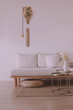 Cargar imagen en el visor de la galería, Assembled Vera clock shown mounted in modern white living room. White walls, white couch with wood accents and metallic round coffee table.