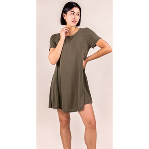 A woman with short black hair stands looking away in a short olive colored t-shirt dress