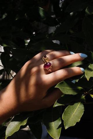 hand with rings reaching towards leaves