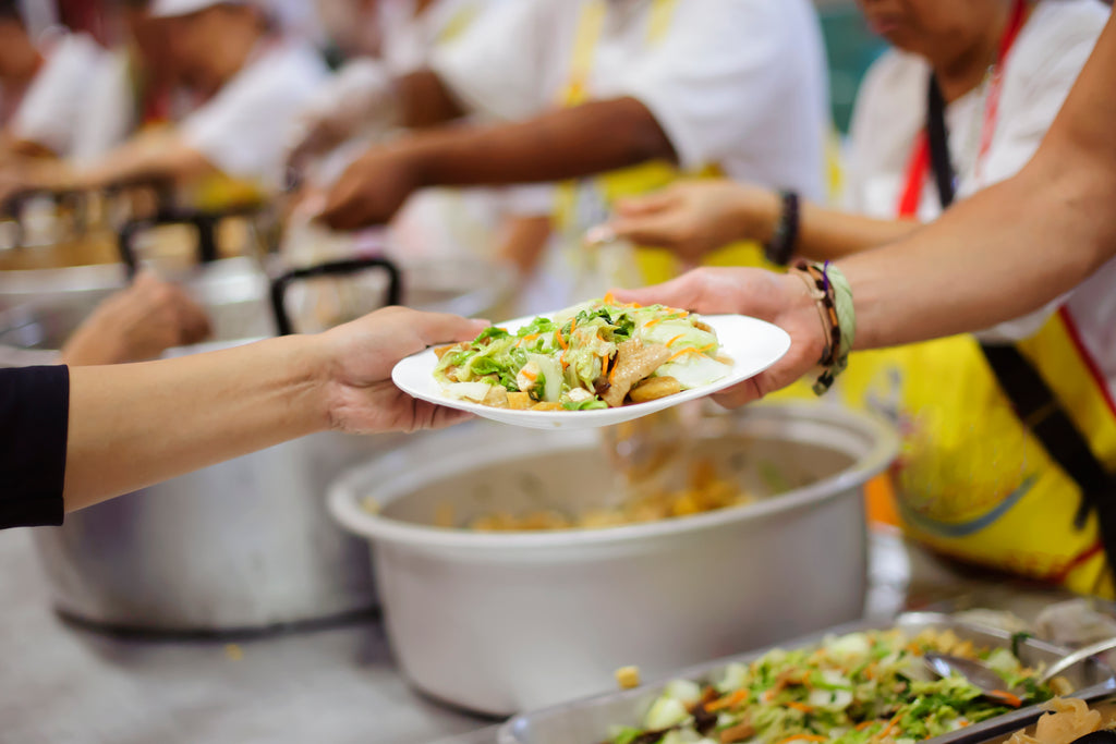 Woman being handed a plate of fruits and veggies in a soup kitchen