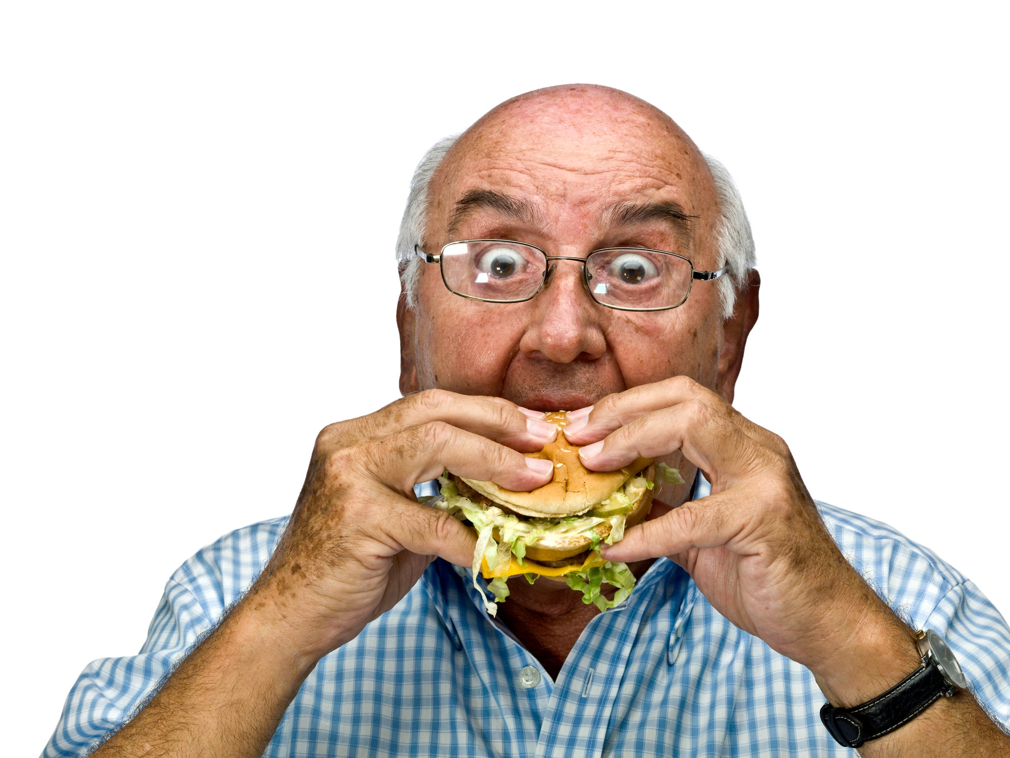 Old man taking a very large bit of a cheese burger filled with bad fats