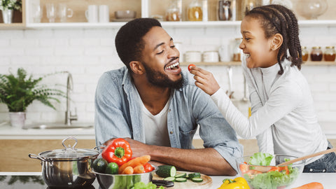 Black father and daughter in the kitchen with vegetables - daughter is feeding vegetables to dad