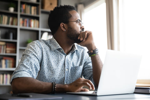 Man in front of laptop looking out the window while he is thinking