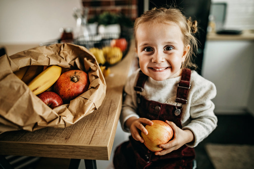Cute little girl smiling holding an apple with fruits and vegetables on the table
