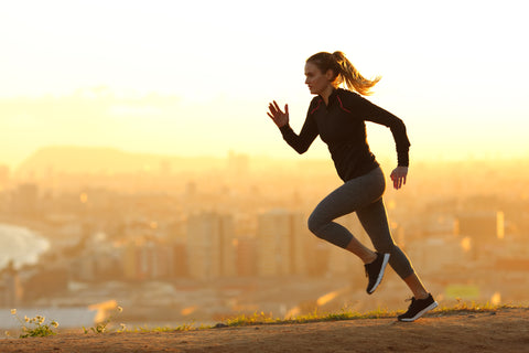 Woman outside exercising and running at sunrise