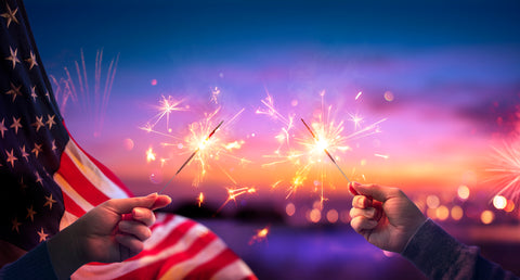 Children holding 4th of July sparklers with an American flag in the backdrop