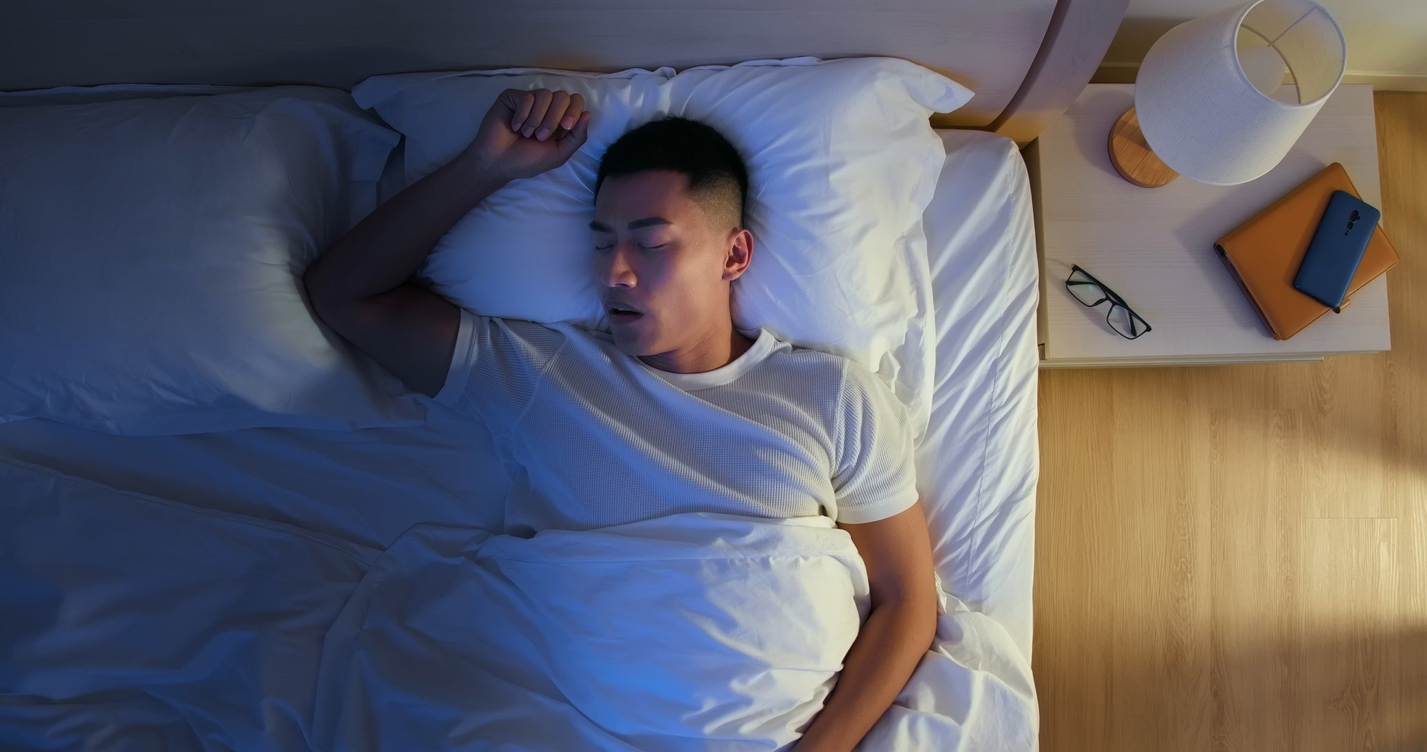 Young man soundly asleep in bed