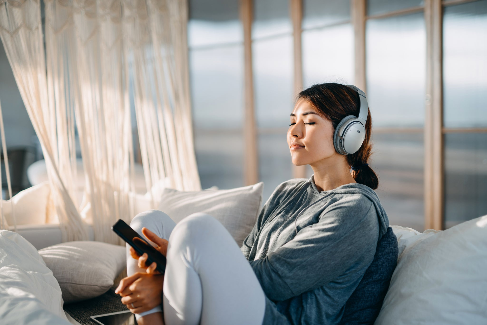 Woman sitting comfortably focusing on music or sounds in headphones
