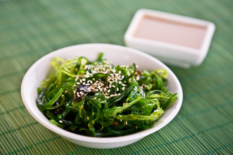 Foods high in omega 3 - White bowl filled with green seaweed and sesame seeds