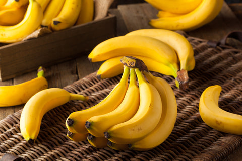 A bunch of yellow bananas set on top of a wicker basket