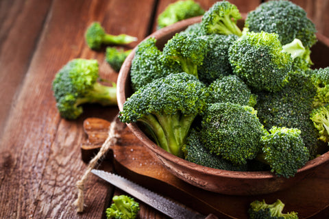 Wooden bowl filled with broccoli that is high in vitamin C