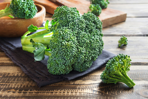 Vegetables high in zinc - broccoli crowns sitting on a wood table