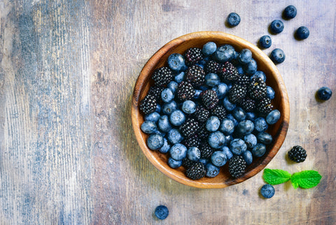 Wooden bowl filled with blackberries and blueberries