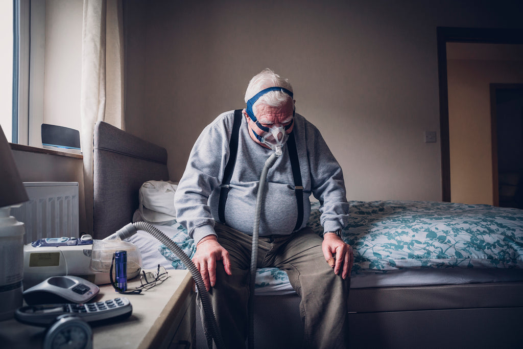Old, sick person sitting on bed using a ventilator - poor health