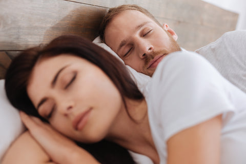 Man and woman sleeping next to each other in bed with white sheets and bright room