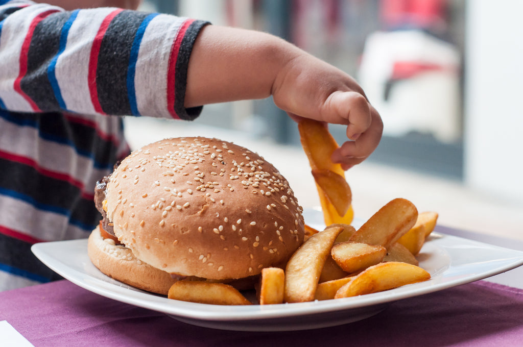 child eating burger and fries - westernized diet