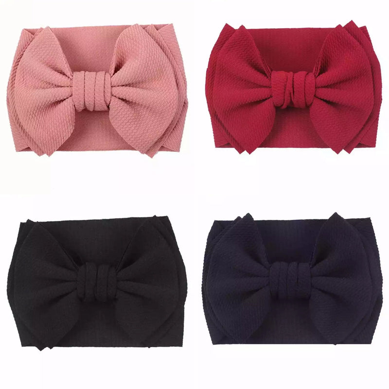 The Izzy Bow Fabric Headband comes in Pink, Red, Indigo and Black.