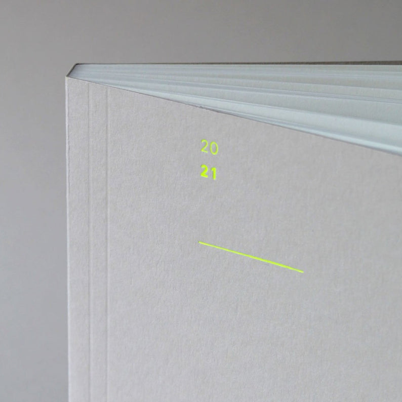 The Mark+Fold 2021 Diary in mist with fluorescent yellow details, featuring our award-winning minimal layout