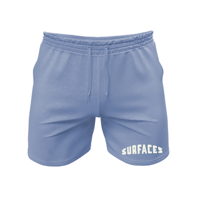 "Blue shorts with a drawstring and an embroidered logo on the bottom of the left leg that reads ""Surfaces""."