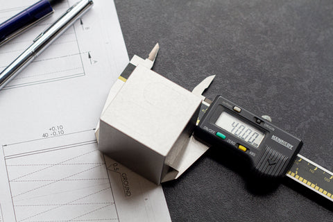 MetMo Cube in calipers on top of technical drawning