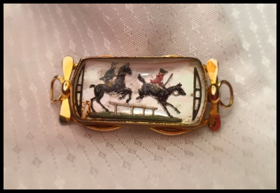 Reverse Crystal Brooch: Antique, hand painted intaglio crystal jumping scene set in 14 kt gold bit style setting