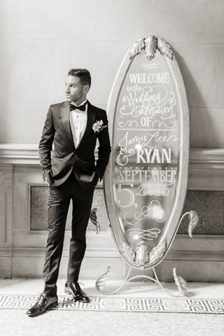 Calligraphy on the rented silver mirror at wedding with groom