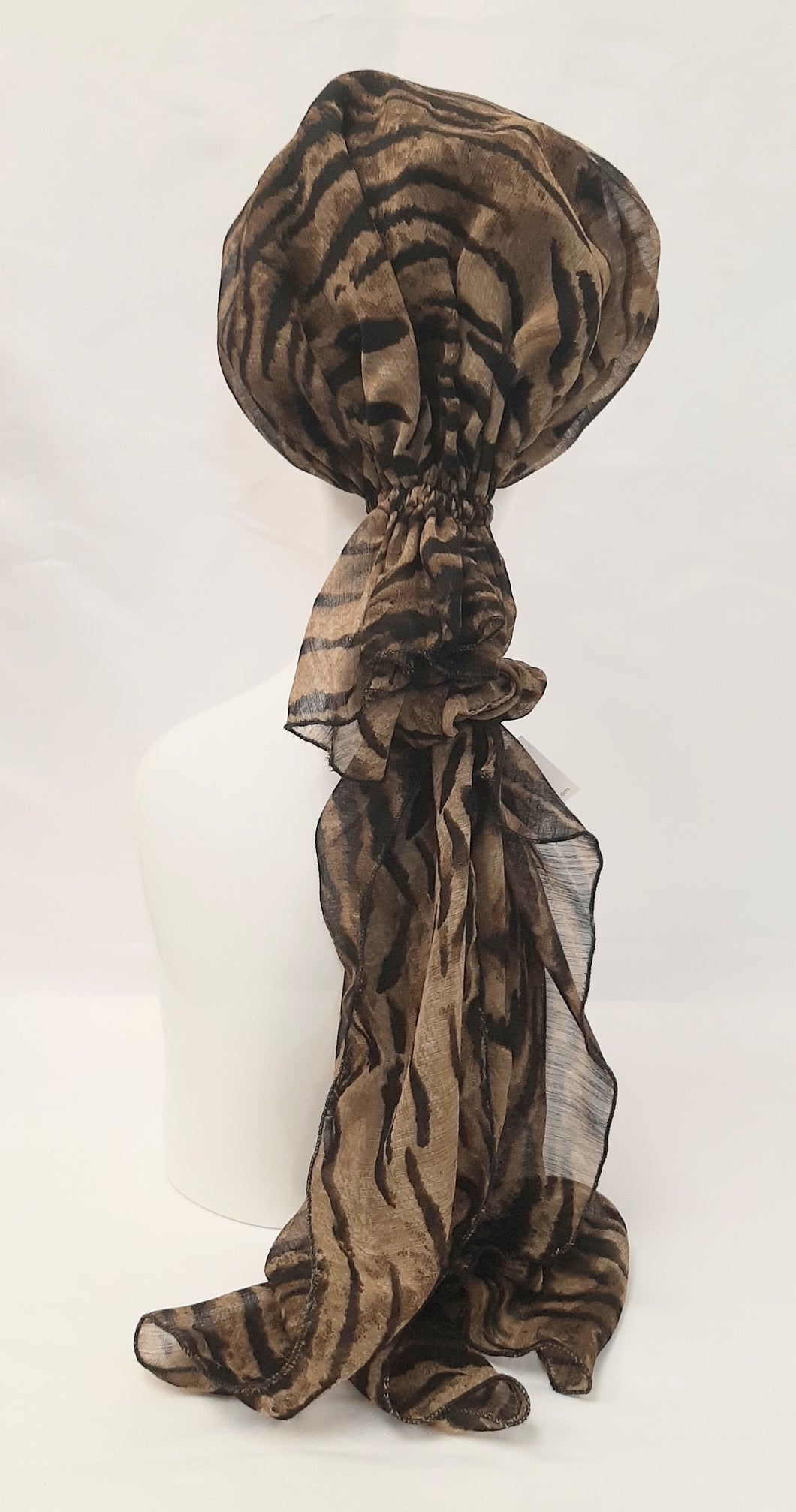 This stylish, very feminine scarf will make you feel gorgeous.  The bonnet is completely lined with cotton/polyester.  There is an elastic casing that makes this scarf comfortable and fits all size heads.  This wonderful scarf can be worn with the tails hanging down the back or layered over the shoulder.  There is a scrunchy that comes with this scarf, to wear over the elastic casing so that you can be creative with taking the tails and making them into a bow for another attractive look.