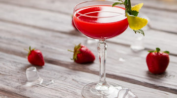 Red fruit cocktail with mint and lemon garnish on a wooden deck with strawberries scattered in the background