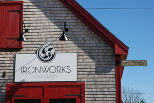 Photo of the red wooden double front door of Ironworks Distillery. The Ironworks sign is above the door. The antique blacksmith shop sign is mounted on the right corner of the building.