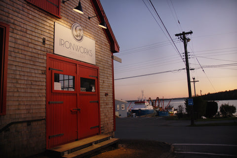 Heritage blacksmith shop in Lunenburg, photographed at sunset with the harbour in the background. A simple 1.5 floor shingled building with big double doors and wooden trim painted red.