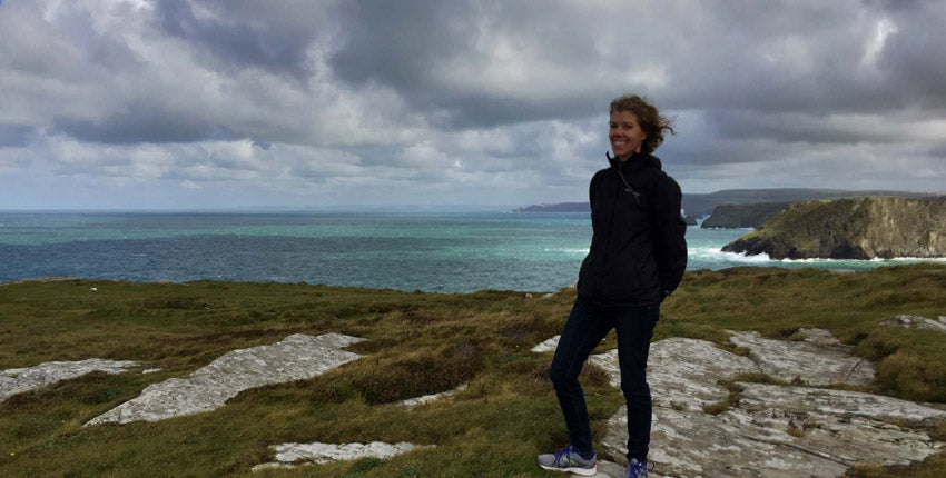 Holly Press Fibers' owner, Elizabeth, glancing at the camera on a wonderfully windy day at Tintagel with the sea in the background.