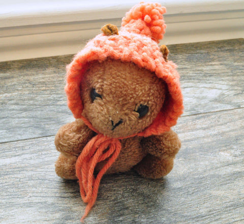 Squirrel stuffed animal with muted orange hand knit bonnet topped with tiny pom pom.