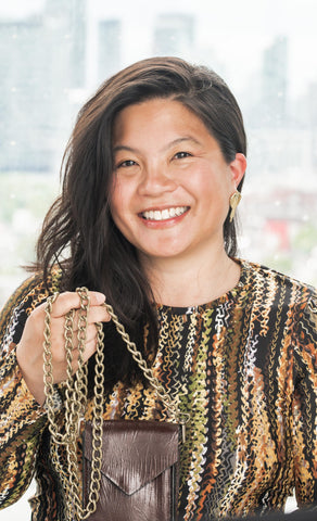 Asian female designer with shoulder length black hair wearing a mixed yellow printed dress is smiling with teeth at the camera and holding up the Convertible Lightpack with the antique brass chain wrapped around her hands.