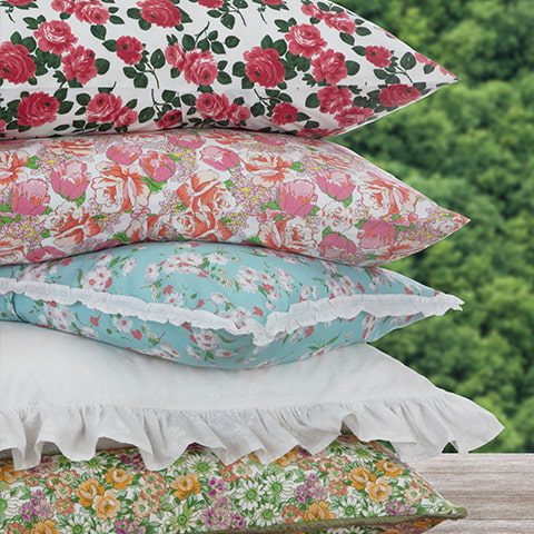 A stack of pillows in Lady Pepperell's floral pillowcases.