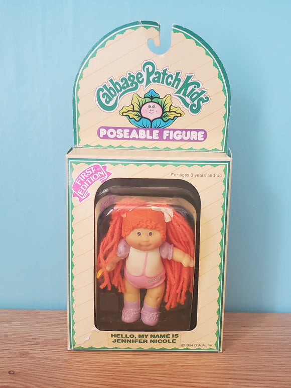 This is a sealed Cabbage Patch figurine who bears the name Jennifer Nicole. She has red yarn hair in two pigtails held together with ribbons, and has blue eyes. Her outfit is purple and white and she is wearing purple socks and shoes. She has a spoon in her right hand. According to the packaging she is a First Edition figure.
