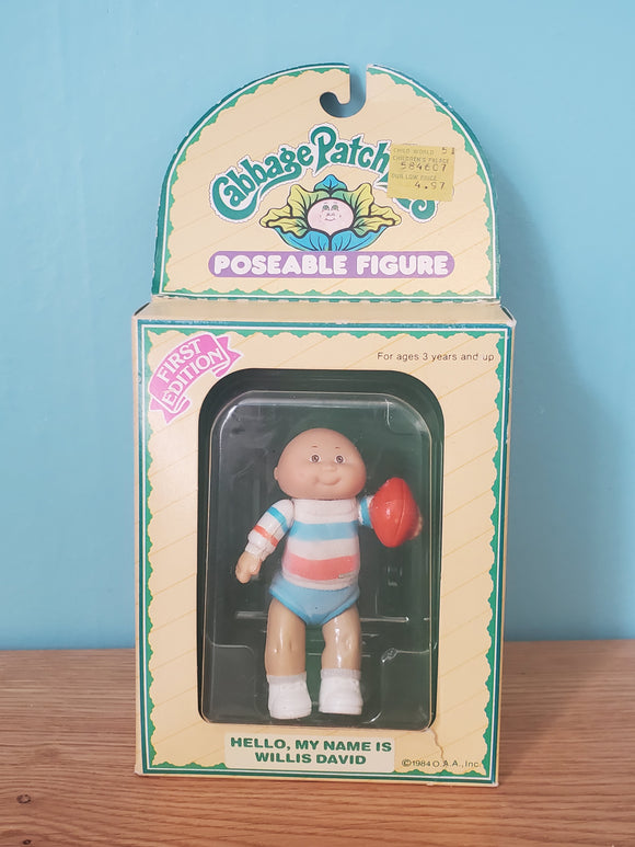 Original Cabbage Patch Kid Poseable Figure Willis David, a bald-headed, brown-eyed cutie, is dressed in a n orange, blue and white striped onesie. It appears as though his outfit was lightly fuzzy at one point, and that the fuzz has worn off over time. Willis is also wearing white socks and shoes. He is holding a football in his left hand.  The card is not in perfect condition. It has some rips on one side of the front.