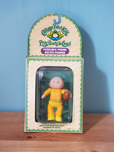 Cabbage Patch Kids Poseable Figure, Thomas Patrick. Figure is wearing a yellow jumpsuit and yellow shoes, and is holding a football. Patrick is bald and has blue eyes. His packaging is in English and French, and is not in perfect condition.