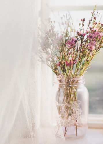 pink flowers in a mason jar sitting in window with sheer curtain
