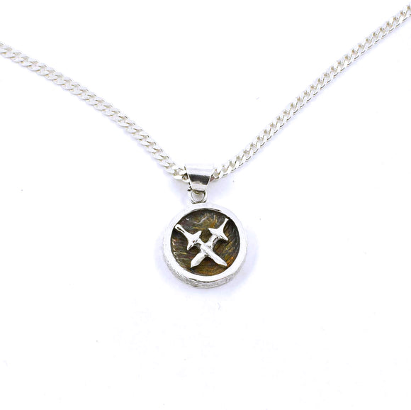 A round sterling silver pendant with two crossed swords on a darkened, textured background.  Made of sterling silver.