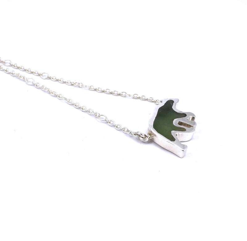 Left side view of sterling silver bear pendant with jade gemstone inlay