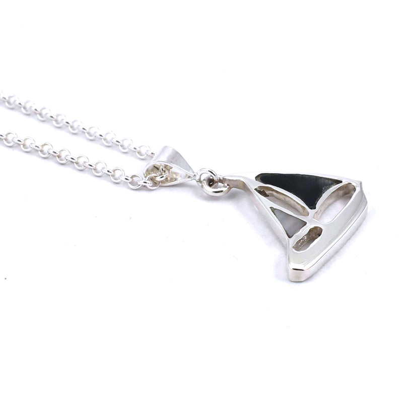 Left side view of sterling silver sailboat pendant with hawkseye and mother of pearl gemstone inlay
