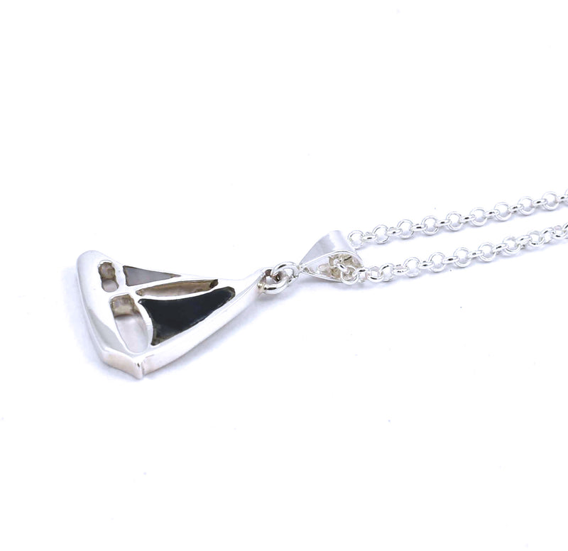 Right side view of sterling silver sailboat pendant with hawkseye and mother of pearl gemstone inlay