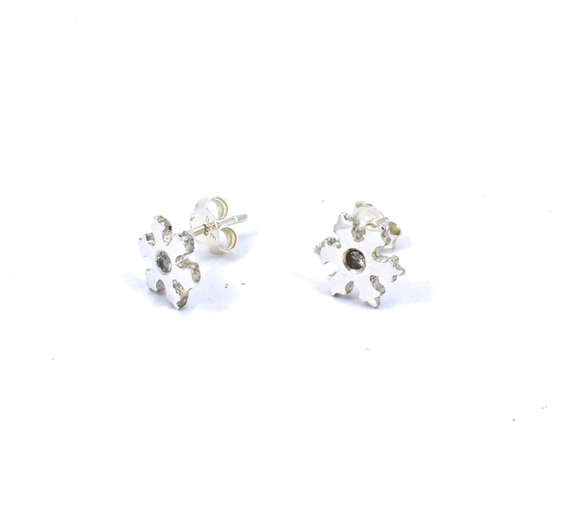 Side view of sterling silver snowflake stud earrings with white sapphires