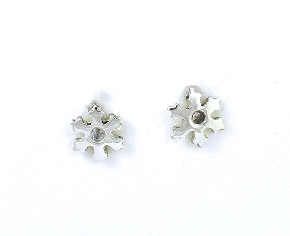 Front view of sterling silver stud earrings shaped like snowflakes with flush set white sapphires.