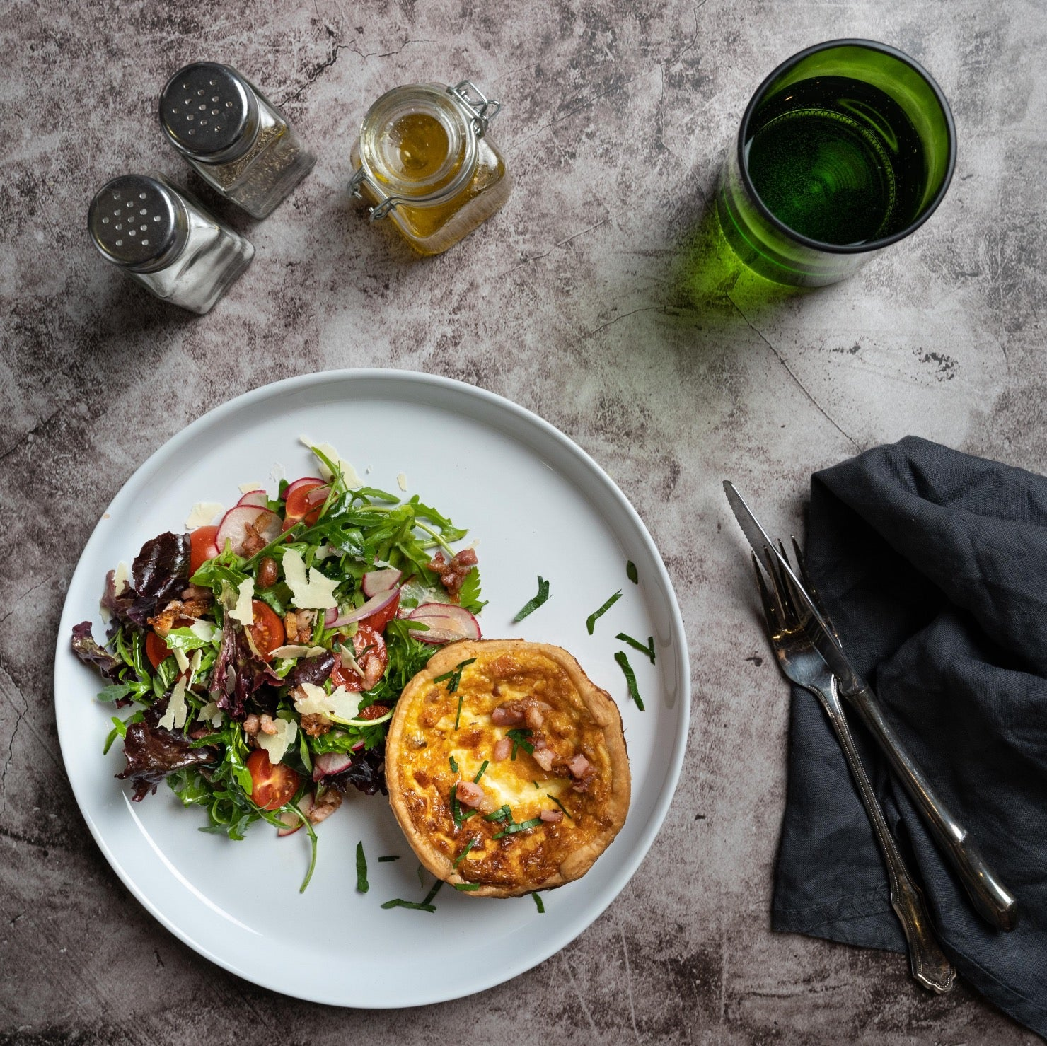 Quiche Lorraine on a plate with a glass of water