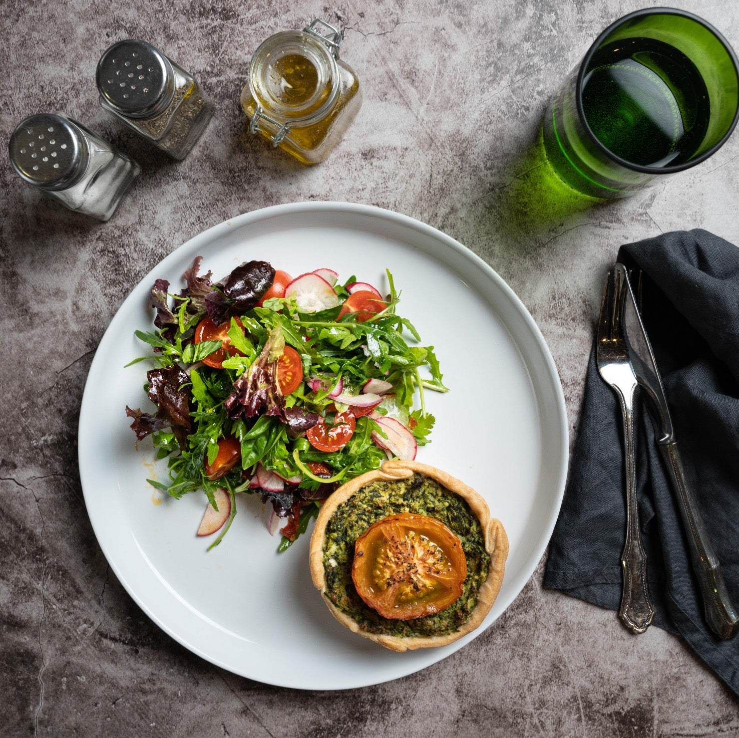 Spinach & Tomato Quiche on a plate with a glass of water