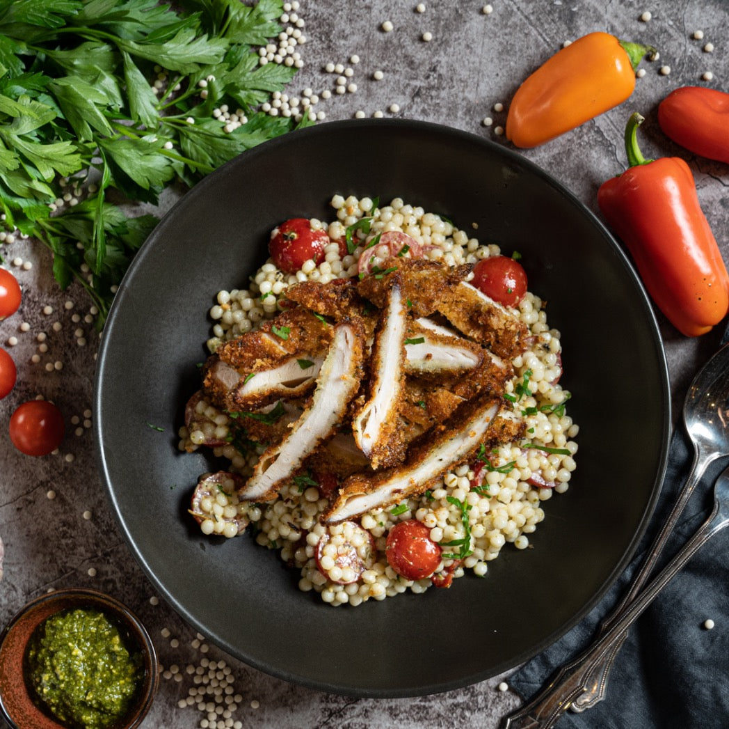 Crumbed Chicken with Pearl Couscous Salad in a plate